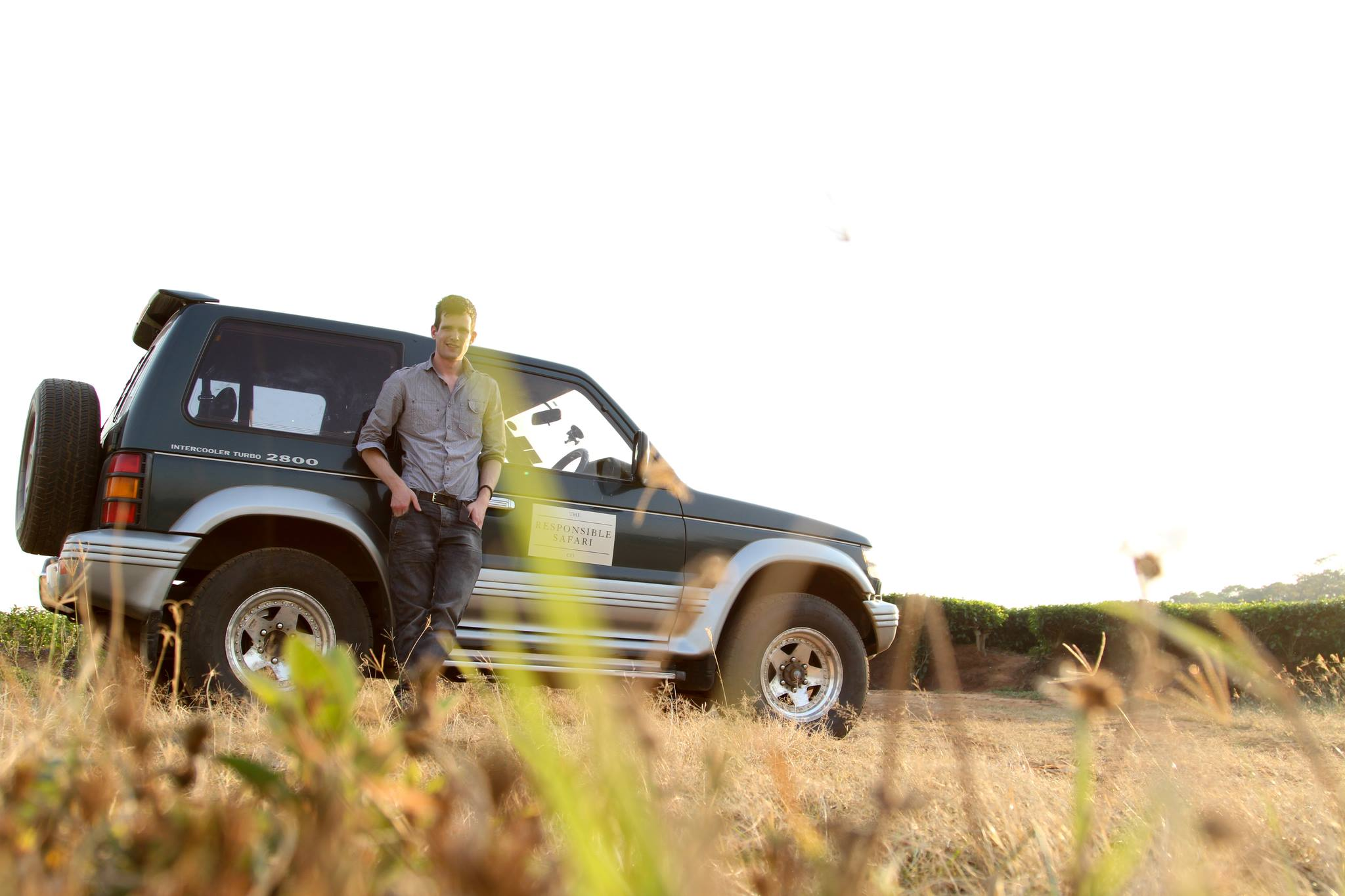 Jonny leaning against his rented 4x4 whilst driving abroad in Malawi